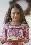 African girl holding plate of cookies - stock photo