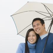 Asian couple hugging under umbrella Stock Photos