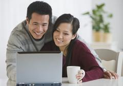 Asian couple looking at laptop Stock Photos
