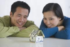 Asian couple looking at house made of money Stock Photos