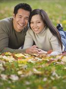 Asian couple laying in grass - stock photo