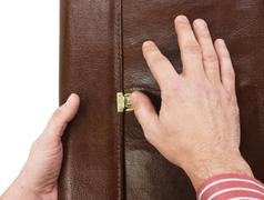 Stock Photo of hand lock buttons on the briefcase