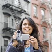 Mixed Race woman holding video camera Stock Photos