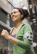Mixed Race woman wearing headphones and jogging Stock Photos