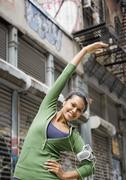 Mixed Race woman stretching in urban area Stock Photos