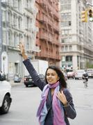 Mixed Race woman hailing taxi cab - stock photo