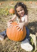 Stock Photo of Hispanic girl sitting with pumpkin