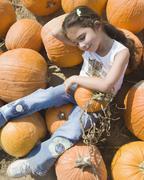 Hispanic girl laying in pumpkin patch Stock Photos