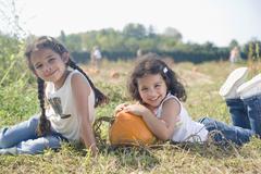 Stock Photo of Hispanic sister sitting next to pumpkin