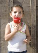 Hispanic girl eating candied apple Stock Photos