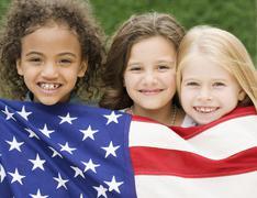 Multi-ethnic girls holding American flag - stock photo