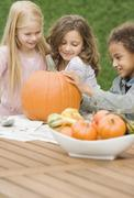 Multi-ethnic girls carving pumpkin - stock photo
