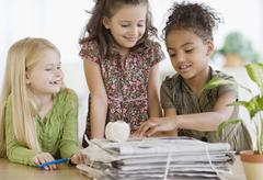 Multi-ethnic girls bundling newspapers Stock Photos