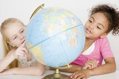 Multi-ethnic girls looking at globe - stock photo