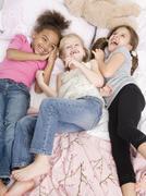 Multi-ethnic girls laying on bed - stock photo