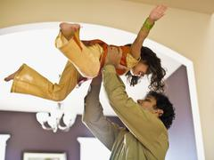 Indian father holding daughter in air Stock Photos