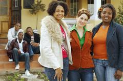 Stock Photo of Multi-ethnic women hugging with friends in background