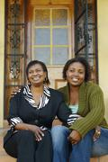 African mother and adult daughter sitting on porch steps - stock photo