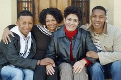 Mixed Race mother and adult children on porch steps Stock Photos