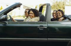 African couples driving in convertible car - stock photo