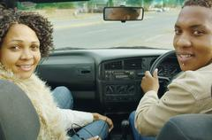 African couple driving in convertible car - stock photo