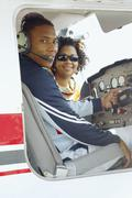 African couple in cockpit of airplane - stock photo