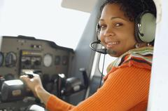 African woman in cockpit of airplane - stock photo