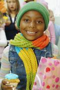 African girl holding cupcake and gift bag Stock Photos