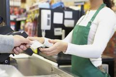 Man paying with credit card at grocery store Stock Photos