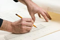 hand draws a pencil on drawing - stock photo