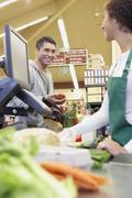 Hispanic man checking out at grocery store Stock Photos