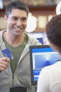 Hispanic man holding up credit card at check out Stock Photos