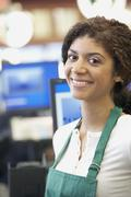 Stock Photo of Mixed Race cashier wearing apron