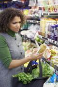 African woman reading label at grocery store Stock Photos