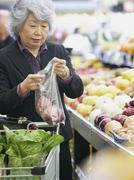 Senior aasialainen nainen ostoksilla tuotteita Kuvituskuvat
