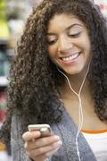 Mixed Race woman listening to mp3 player Stock Photos
