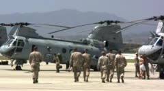 US Marines walking toward choppers Stock Footage