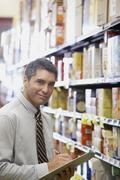 Hispanic grocery store manager holding clipboard Stock Photos