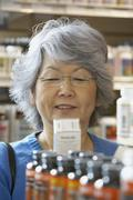 Senior Asian woman reading vitamin label - stock photo