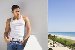 Hispanic man leaning on balcony wall - stock photo