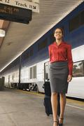 African businesswoman pulling suitcase as train station Stock Photos