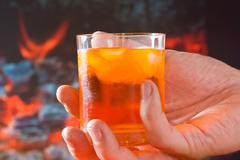 glass of drink in his hand - stock photo