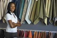 African woman next to fabric swatches Stock Photos