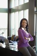African businesswoman sitting on edge of desk - stock photo