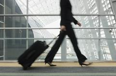 Businesswoman pulling suitcase Stock Photos