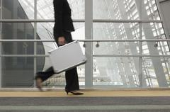 Businesswoman carrying briefcase - stock photo