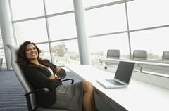 Hispanic businesswoman next to laptop Stock Photos