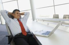 Hispanic businessman with hands behind head Stock Photos