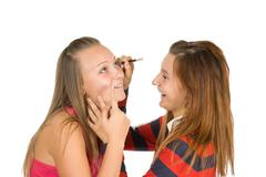 Stock Photo of two teenage girls dye their eyelashes