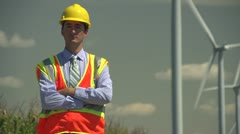 Engineer standing in front of windmills Stock Footage
